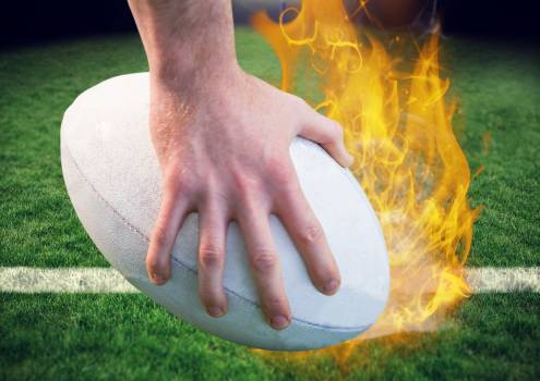 Hand holding a rugby ball with flames on pitch in stadium #412843