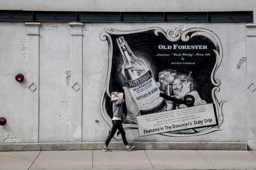 Person Walking Along Concrete Wall With Old Forester Bottle Graffiti Free Photo