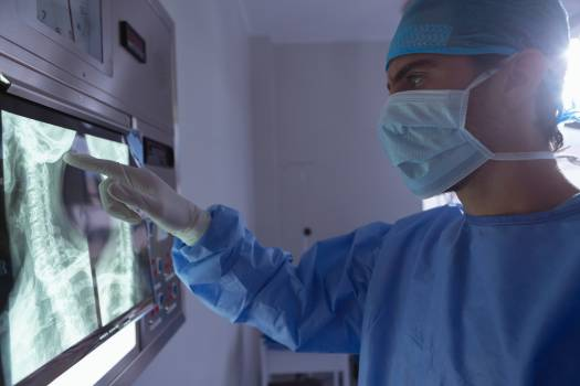 Male surgeon examining x-ray on x-ray light box in operation room at hospital #412855