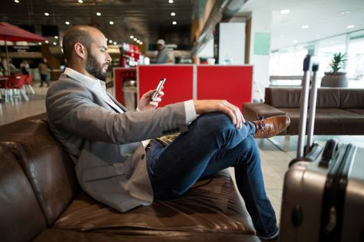 Businessman using mobile phone in waiting area Free Photo