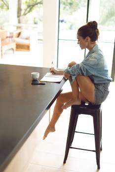 Woman writing on notepad on worktop in kitchen at comfortable home Free Photo