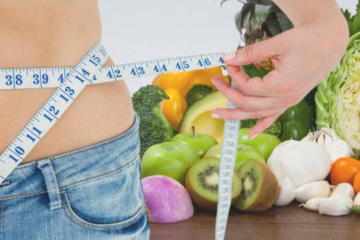 Midsection of woman measuring waist against fruits and vegetables representing weight loss #412922
