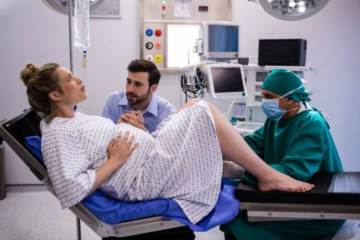 Doctor examining pregnant woman during delivery while man holding her hand #412932