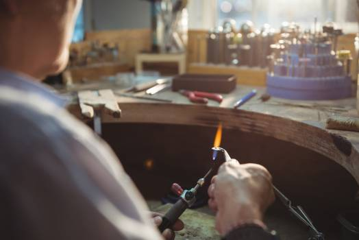 Craftswoman using blow torch in workshop Free Photo