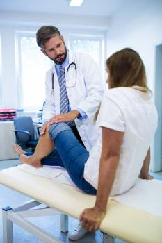 Male doctor examining patients knee #412946