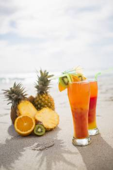 Two glasses of cocktail drink and tropical fruits kept on sand #412955