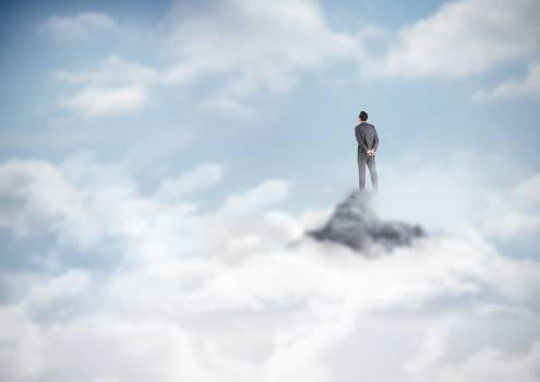 Business man standing on mountain peak in the clouds Free Photo
