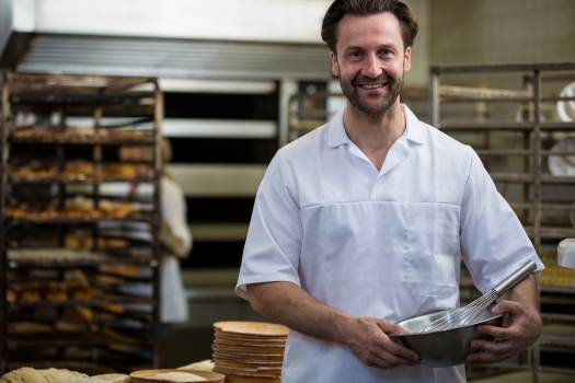 Smiling baker holding a bowl and a whisk Free Photo