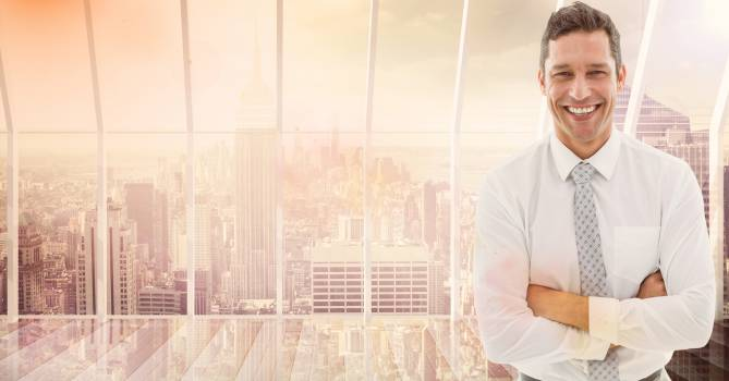 Smiling businessman standing with arms crossed against cityscape in background #412994