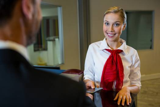 Female staff giving boarding pass to the businessman #413022