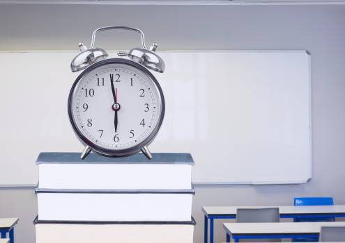 Digital composition of alarm clock on books in classroom #413032