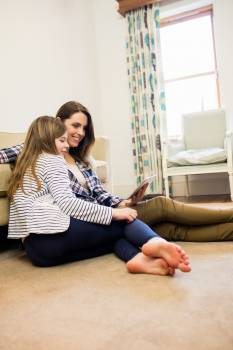 Mother and daughter using digital tablet in living room #413054