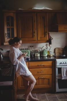 Woman using mobile phone while having coffee in kitchen #413081