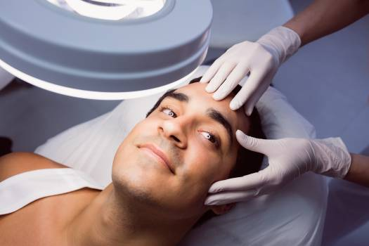 Doctor examining mans face for cosmetic treatment #413099