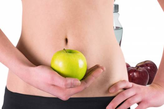 Midsection of woman holding Granny Smith apple in front of abdomen #413107