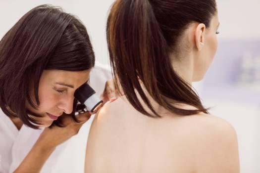 Dermatologist examining skin of patient with dermatoscope #413129