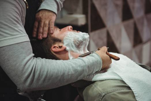 Man getting his beard shaved with razor Free Photo