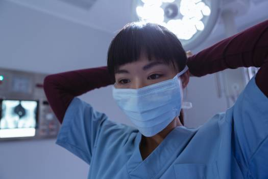 Female surgeon wearing surgical mask in operation room at hospital #413141