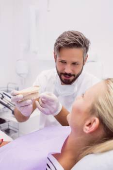 Dentist showing denture model to the patient #413151
