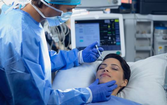 Surgeon giving injection to the face of a female patient in operating room Free Photo