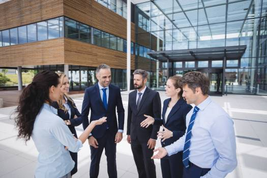 Group of businesspeople interacting outside office building Free Photo