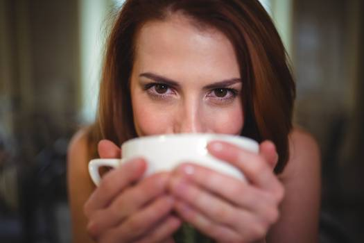 Beautiful woman having a cup of coffee in café Free Photo
