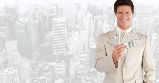 Portrait of smiling businessman holding fanned currency Free Photo