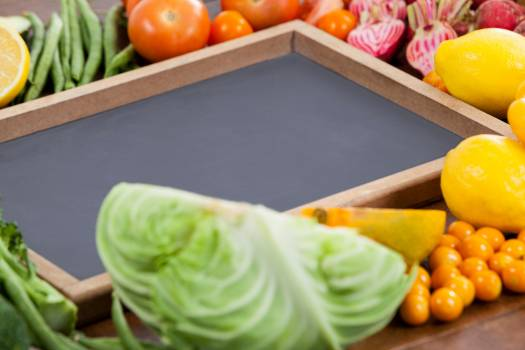 Wooden tray surrounded with fresh vegetables #413239