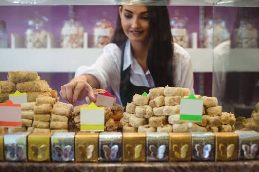 Female shopkeeper arranging turkish sweets at counter #413247