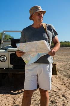 Man looking way while holding map on field #413250
