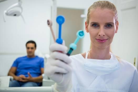 Smiling dentist holding dental tools  Free Photo