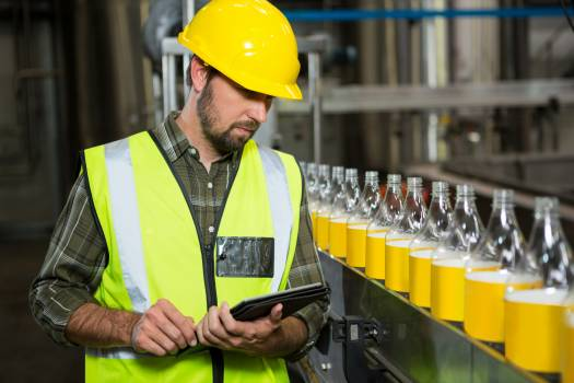Male worker using digital tablet in juice factory #413310