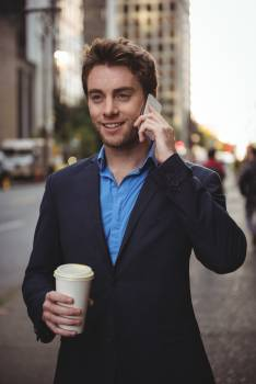 Businessman talking on mobile phone and holding coffee Free Photo