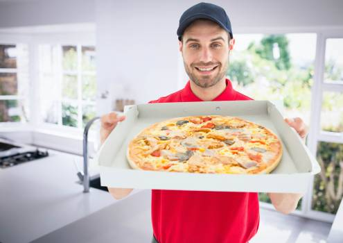 Happy deliveryman showing the pizza in the kitchen #413341