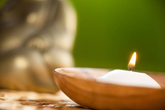 Lit candle in wooden bowl #413365