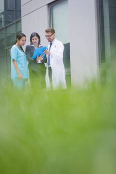 Doctors and nurse discussing over report Free Photo