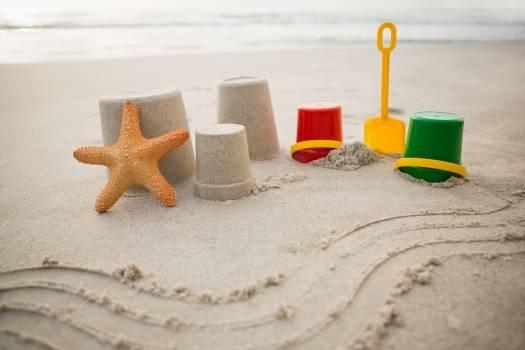 Bucket, spade, starfish and sand castles on beach Free Photo