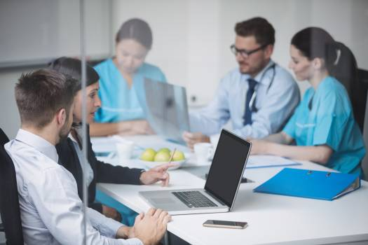 Doctors discussing over laptop in meeting Free Photo