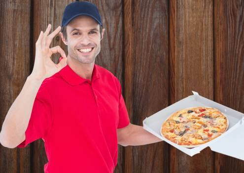 Happy deliveryman with pizza. Wood background #413445