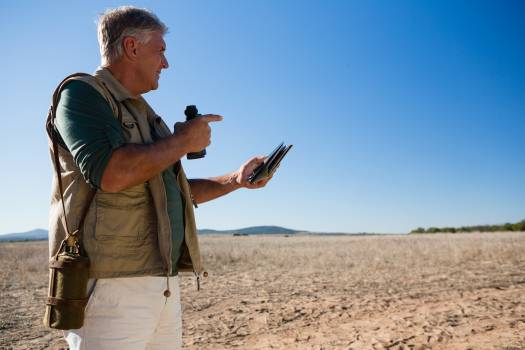 Man with map and binocular looking away on landscape Free Photo