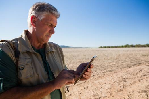 Man using digital tablet on landscape #413454
