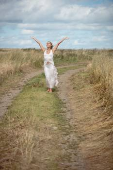 Carefree blonde woman standing on the field path Free Photo