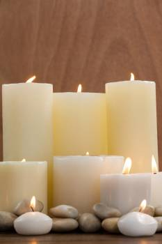 Close- up of white candles and pebbles stone on wood #413477