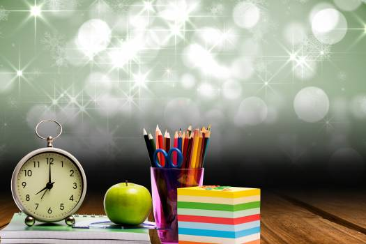 school materials and alarm clock with starry background #413480