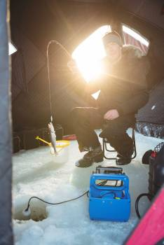 Ice fisherman sitting on chair with fish in his rod #413483