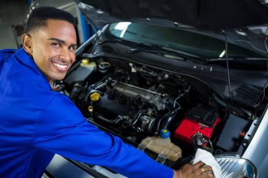 Happy mechanic servicing car #413488