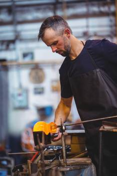 Glassblower forming and shaping a molten glass #413497