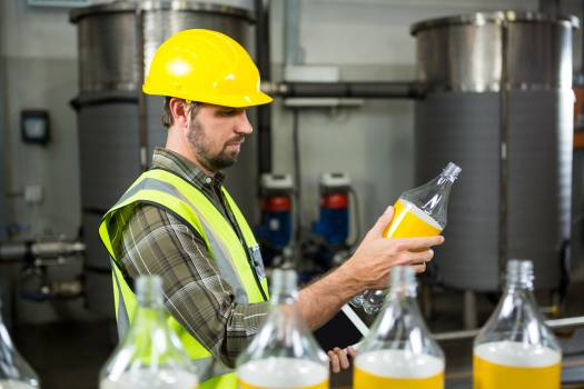 Serious male worker inspecting bottles in juice factory #413534