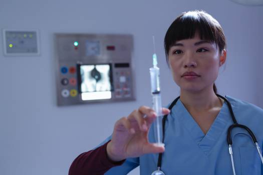 Female surgeon looking at syringe in operation room at hospital #413555