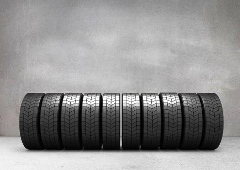Tyres arranged in a row against concrete wall #413596